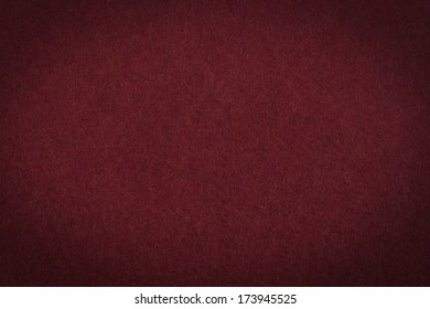 Maroon paper background or texture with vignette