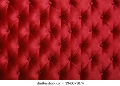 Maroon red velvet capitone textile background, retro Chesterfield style checkered soft tufted fabric furniture diamond pattern decoration with buttons, close up