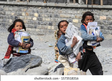Marpha, Nepal - March 20, 2014: A group of little poor Nepalese children of boys and girls walk along a village street in the Himalayas and carry school books. Poor children of Nepal