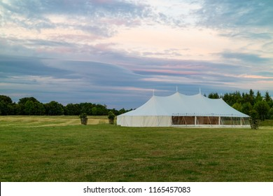 A marquee set up in a field in the evening for an event like a wedding or a party