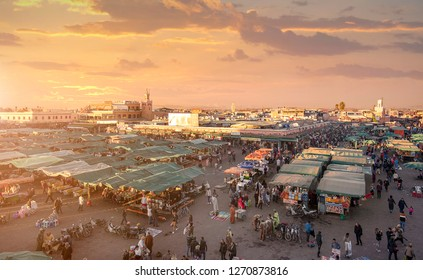 Marrakech, Morocco - 22 December 2018: People visit the Djemaa el Fna ( Jemaa el Fnaa ) famous Square and market place at sunset. The square in Marrakesh medina is part of the UNESCO World Heritage.