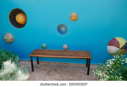 Marrakech, Morocco, 24.04.2018. Bench in front of blue wall in Anima, Andre Heller's imaginative garden.