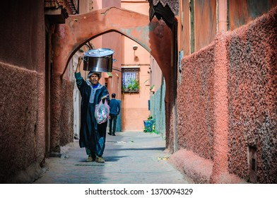 MARRAKECH, MOROCCO - APRIL 12, 2017: Local man with a huge pot on his head in the Medina of Marrakech, Morocco