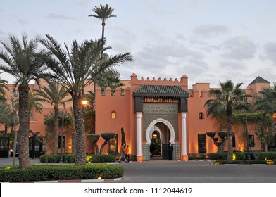 Marrakech, Morocco - april 24, 2016: Palm trees and main facade of the famous hotel of La Mamounia, in the historic center of the city, at dusk