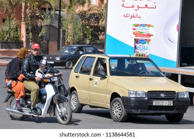 Marrakech, Morocco - april 24, 2016: Young man with his family on board a motorcycle next to a petit-taxi circulating along an avenue of Ville Nouvelle, the most modern area of the city