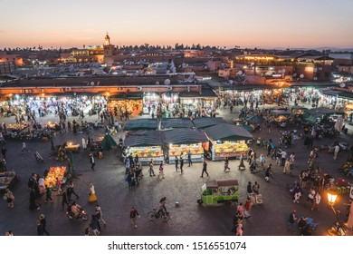 Marrakech, Morocco - APRIL 26 2019: salesman and tourists seen from a terrace in the beautiful colors at sunset in center of Medina