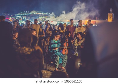 Marrakech, Morocco - circa July 2017:  Violin player at Djemaa el Fna square with crowd of people and smog of the market