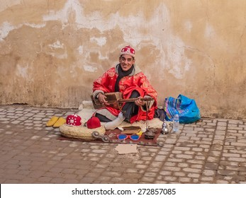 Marrakech, Morocco - December, 08, 2012: Moroccan Gnawa street musician playing gumbri in the streets of Marrakech