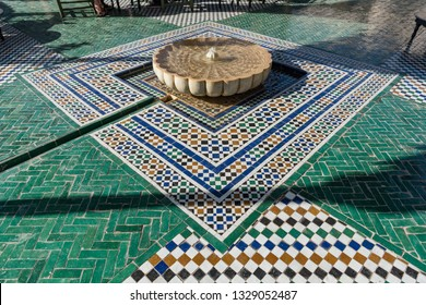 MARRAKECH, MOROCCO - FEBRUARY 7, 2019: Decorative floor tiles and fountain in a courtyard garden, Marrakech, Morocco. Zellige floor tiles at the Secret Garden, Marrakech.