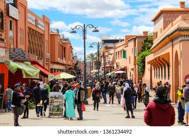Marrakech, Morocco / Friday April 2019 A busy street in the Marrakech Médina of Morocco filled with people both locals and tourists browsing  shops and street vendors and bright blue skies
