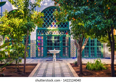 Marrakech, Morocco - January 10, 2019 : Small white fontaine among orange trees of Jardin Majorelle in Marrakech, Morocco