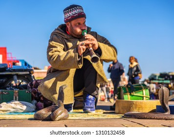 Marrakech, Morocco - January 11, 2019 : Snake charmer plays music for his cobra at the Jemaa el-Fnaa square in Marrakesh