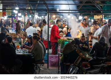 MARRAKECH, MOROCCO - JANUARY 2, 2018: People preparing food and others are eating in food stalls at square Jemaa el Fna in Marrakech in Morocco