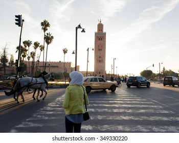 MARRAKECH, MOROCCO - OCTOBER 27, 2015:  Woman crossing street at Marrakech medina near the UNESCO square Djemaa El-fna at Marrakesh, Morocco