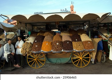 MARRAKESH – CIRCA FEB 2009: Two street vendors stand by dried fruit stall at Djemaa el Fna square in Marrakesh, Morocco circa February 2009. The market is frequently visited by locals and tourists.