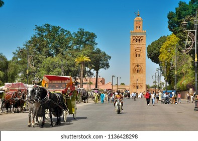 Marrakesh, Morocco - 2 July 2018: Koutoubia minaret made from golden bricks in centrum of medina. Frontal view on tower. Iconic center of Marrakesh. Horse carriage with passenger