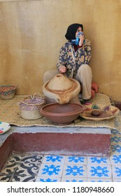 Marrakesh, Morocco - 2016-03-02 : Woman working to grind argan nuts to make oil, butters and other products, near Marrakesh, Morocco, Africa