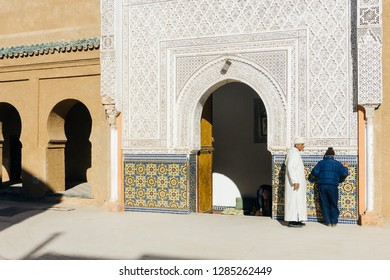 Marrakesh, Morocco - January 13: 2019. Marrakesh medina (Marrakech medina). Zaouia Sidi bel Abbes mosque Marrakech. Two persons near the mosque in Marrakesh