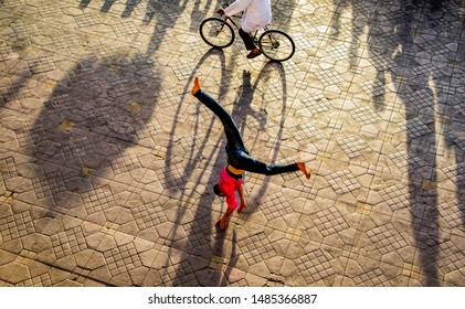 MARRAKESH, MOROCCO – June 01, 2019.: Stretched long late afternoon shadows of the walking people,and an acrobat cartwheeled at the Jemaa el-Fnaa or  Djema el-Fna  market square.