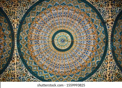 MARRAKESH, MOROCCO - JUNE 7, 2019 Detail of wooden ceiling at Bahia Palace painted with colorful floral Arabic circular patterns with predominant blue, yellow and green colors