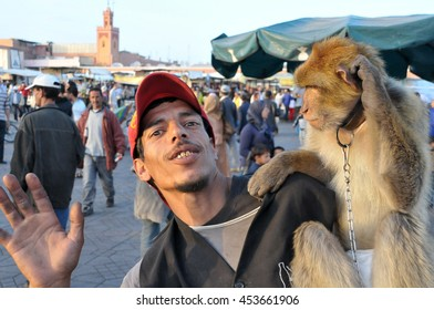 MARRAKESH, MOROCCO - MARCH 16, 2012: Puppeteer with his trained monkey, draws the attention of people in the Jemaa el Fna