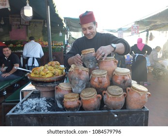 MARRAKESH, MOROKKO. MARCH 2018. Jamaa el Fna market square. Traditional Moroccan tajin with meat and vegetables. Man cooks it on charcoal