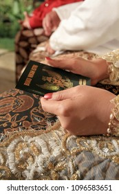 Marriage couple hold the Buku Nikah, a legal statement book for wedding in Indonesia