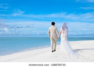 Marriage coupll wearing a suit and white wedding dress walking in the beach