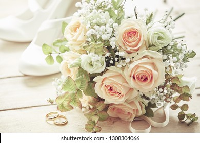 Marriage day setting with bridal bouquet of pink roses, white brides shoes and wedding rings sitting on wooden surface, viewed in close-up