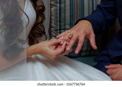 Marriage hands with rings. The bride puts a ring on the finger of the groom during the wedding ceremony. The bride and groom exchange rings in wedding day. Photo closeup