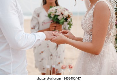 Marriage hands with rings. Bride wears the ring on the finger of the groom during wedding ceremony on the beach