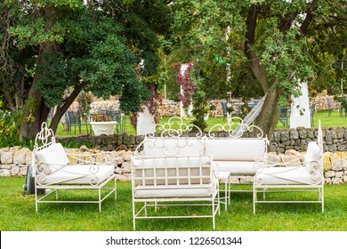 Marriage in a masseria in Puglia (Italy). A garden with chairs and sofa for guests on the green lawn.