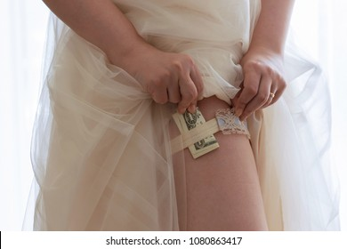 Marriage for money / gold digger concept: detail of a bride putting money under her wedding garter