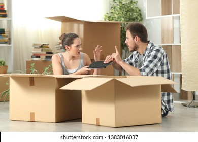 Marriage moving home fighting for a tablet sitting on the floor