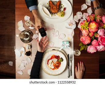 Marriage offer at a table with wine and flowers