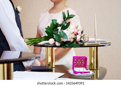 Marriage registration ceremony, newlyweds are visible in the background, focus on wedding rings and bridal bouquet
