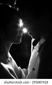 Married bride and groom dancing in a backlit scenario. Tenderness and happy family. Just married. First dance. Black and white image
