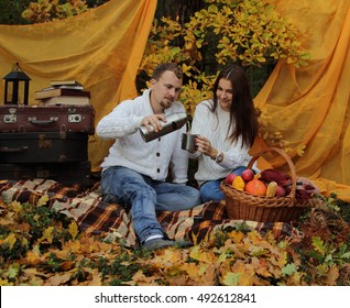 married couple in the autumn wood on a picnic give some tea in a cup