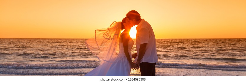 Married couple, bride and groom, kissing at sunset or sunrise on a beautiful tropical beach wedding panoramic web banner