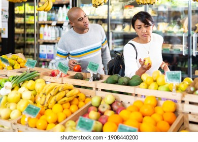 Married couple choosing fruits in grocery store