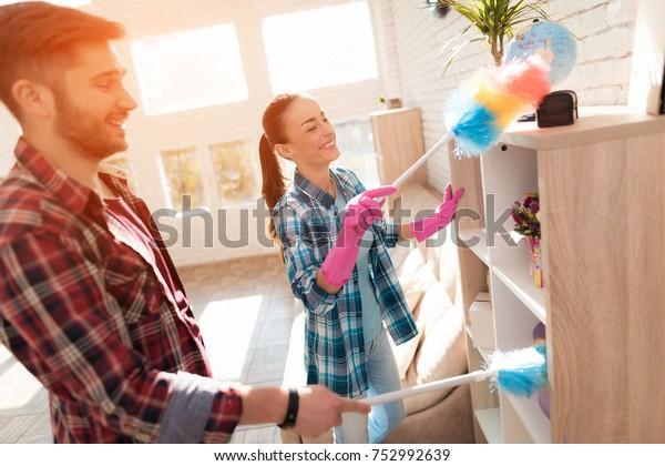 アパートを掃除する夫婦。彼らはほこりを払う。彼らは家具と本棚を汚れから掃除する。ゴム手袋、スポンジ、水噴霧器、防塵ブラシを使用します。