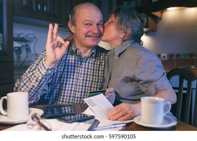 A married couple counts money and a budget. The wife kisses her husband's cheek. He  shows the sign okay.