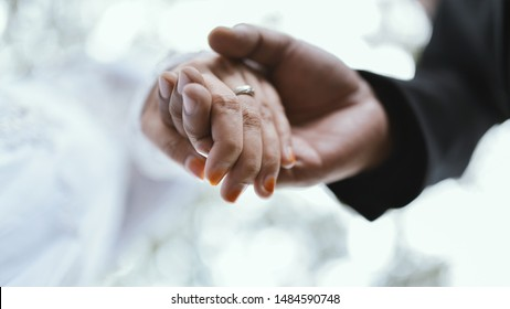Married couple holding hand at ceremony wedding