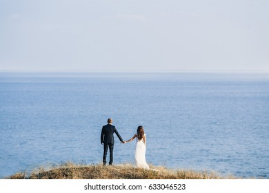 married couple holding hands in a beautiful sea landscape