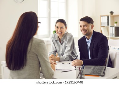 Married couple in the office at a consultation meeting in a friendly atmosphere talking to the bank manager. Husband and wife negotiate the first purchase of a house or take a loan.