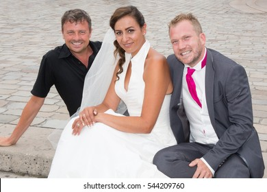 A married couple poses with a man during their wedding photos