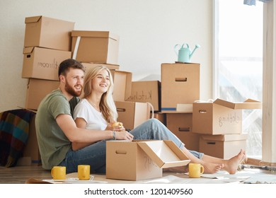 married couple sitting near cardboard boxes in new apartment relaxing after unpacking boxes
