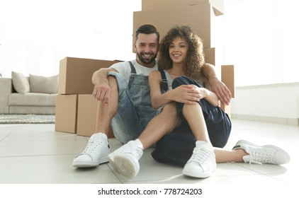 married couple sitting near cardboard boxes in a new apartment