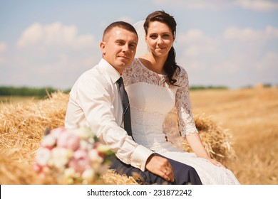 married couple sitting on haystack at summer