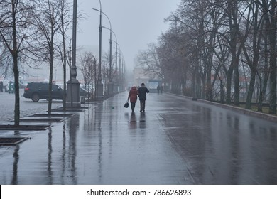 A married couple is walking around the city after a rain. Winter landscape.